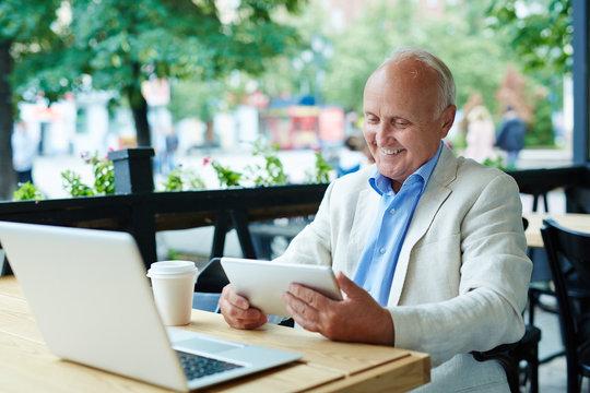 Pleased Senior Looking at Tablet Screen
