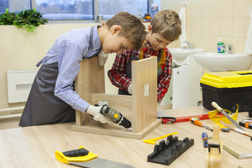 children in the workshop construct wooden stool using a drill and a screwdriver