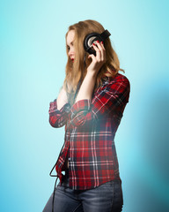 beautiful girl posing on a green background. Blonde girl in a plaid shirt and jeans listening to music. girl in headphones with red lips and red nail polish. artistic portrait