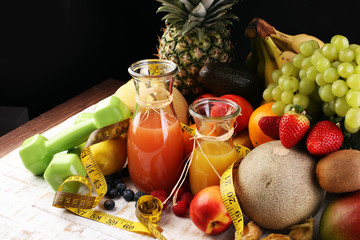 Healthy lifestyle concept. measuring tape sport fitness equipment and healthy food and juice (fruits and vegetables, dumbells, apple, kiwi, pineapple,lemon strawberry