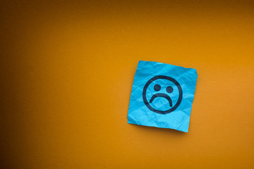 Blue paper note with sad face on a yellow paper background