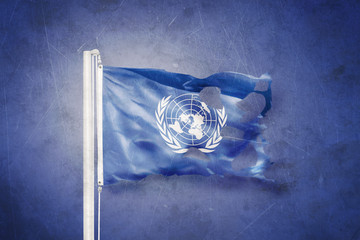 Torn flag of the United Nations waving against grunge background