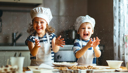 Foto op Canvas Koken happy family funny kids bake cookies in kitchen