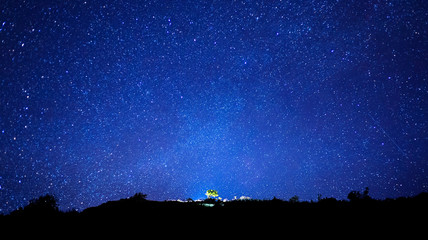 Milky Way and silhouette of tree on top of mountain, Long exposu