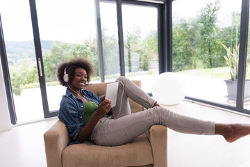 African american woman at home in chair with tablet and head pho