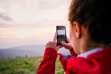 Woman hiker taking photo with smartphone at mountain peak. Female hiker shoting photos in warm evening light during a sunset.