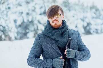 stylish man with a beard in snowy winter forest