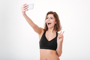 Fitness woman showing peace sign and taking selfie with smartphone