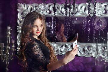 Beautiful smiling girl making selfie in luxury modern interior.