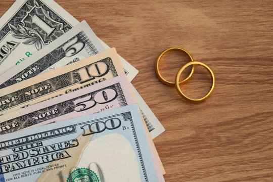Golden wedding rings on Dollar banknotes cash background. Marriage of convenience