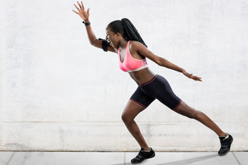 Full length action portrait of muscular african female athlete in running position. Side view of young woman shouting at take off. Girl in sportswear against light grey concrete background.