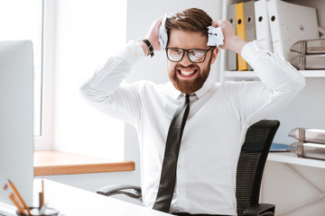 Confused businessman sitting in office and holding paper