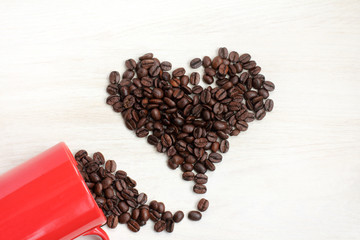 one hundred percent genuine love/ coffee beans spilled out from a cup on the table, heart shaped top view