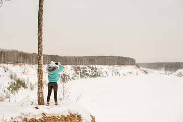 Girl in bright clothes on the edge of the cliff on the background of the winter forest in winter. In the hands of the phone, take pictures on the phone