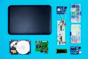 Top view of desktop of  hardware engineer on blue background. Black laptop with connectors, microcontroller, hdd and hardware equipment