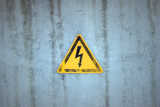 Yellow electricity warning sign on a weathered background