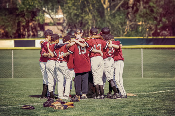 Baseball team in a huddle before a game.  Instgram toned image.