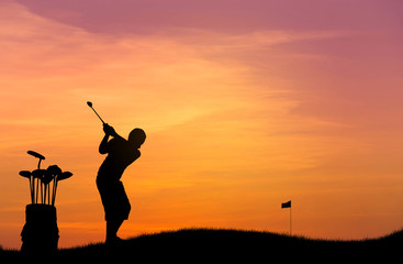 silhouette the golfer hit golf ball toward the hole at sunset with leather baggage metal golf clubs