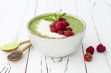 Matcha green tea chia seed pudding bowl, vegan dessert with raspberry and coconut milk. Copy space