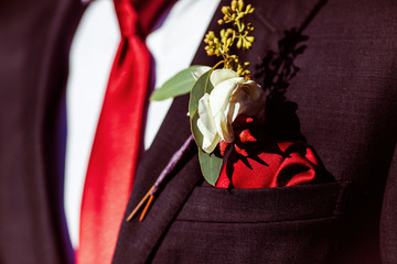 The buttonhole for groom hanging on the costume