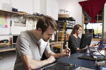 A young man and woman working at a bench in a technology lab.