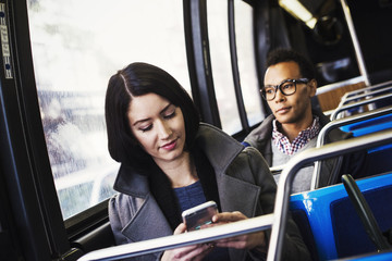 A young woman and a young man sitting on public transport, one looking at a cellphone and one looking away.