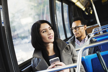 A young man and a young woman sitting on public transport holding their cellphones and looking around.