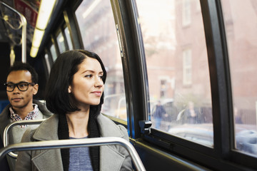 A young woman sitting on a train looking out of the window at an urban landscape, with a man sitting behind her looking away.