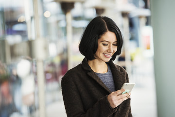 A young woman holding at a cellphone and smiling.