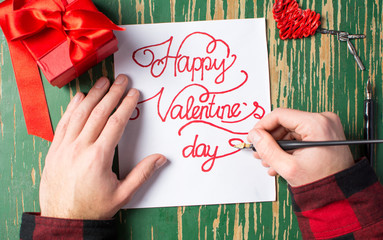 Man writing a Valentines day card and preparing present