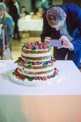 guest at the wedding cake making a picture of fresh fruit
