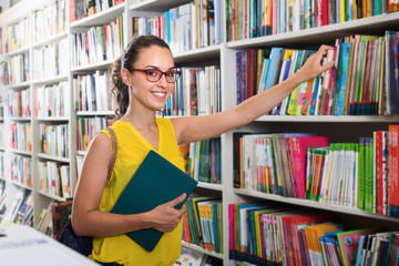 Smiling woman buying books in hard cover