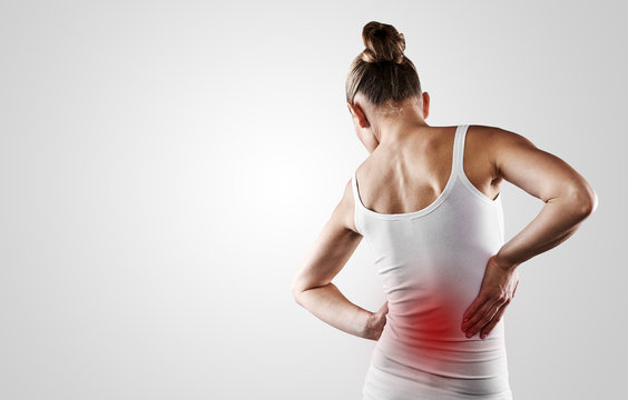 Portrait of young woman touching her painful back over grey background with copy space. Concept of  backbone disease therapy.