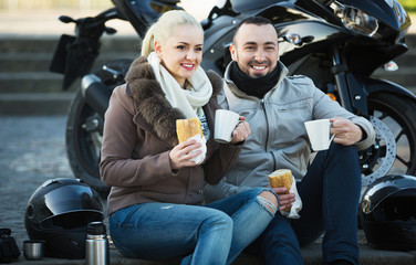 Cheerful  smiling couple having picnic with coffee