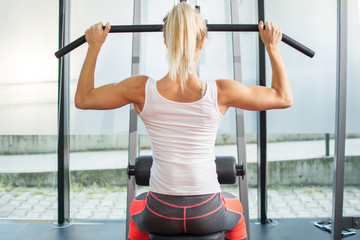 Young blonde woman doing back strengthening exercises in the gym.