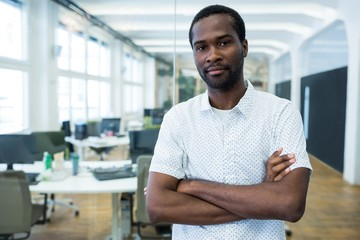 Graphic designer standing with arms crossed in office