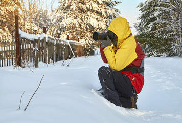Professional photographer taking photos in village in cold winter weather sitting on snow