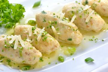 Deftige Südtiroler Kasnocken mit gebräunter Butter und Parmesen auf weißer Platte serviert - South Tyrolean cheese dumplings made of white bread and mountain cheese, served with melted butter