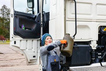 Junge, hübsche Frau, füllt Flüssigkeiten an einem LKW auf