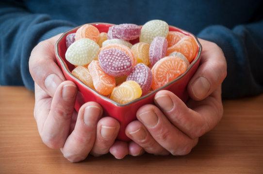 détail main d'homme tenant un bol en forme de coeur contenant des bonbons