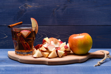 glass with juice, pieces of apple, cinnamon on cutting board