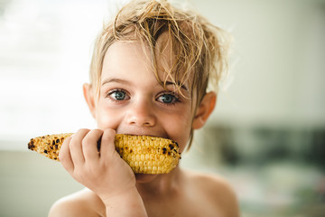Boy eating corn cob