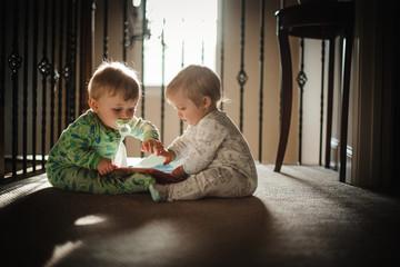Twin babies playing on carpet