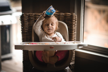 Messy girl sitting in highchair covered in food