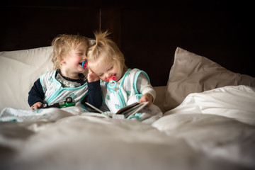 Twins laughing on bed