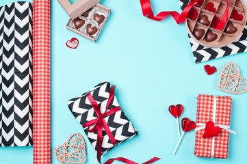 Gift boxes wrapped in red, black and white paper with candy. Flat lay. Valentines day, Christmas (xmas) or New year gift packing. Holiday decor concept.