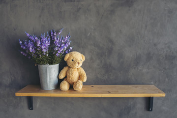 Cute teddy bear with violet flowerpot,teddy bear sitting on wooden floor against cement wall background.