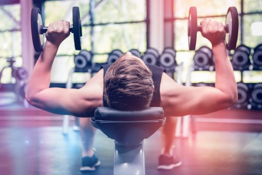 Man lifting dumbbell weights while lying down