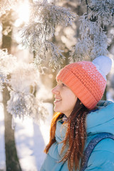 Woman portrait in winter forest at sunset