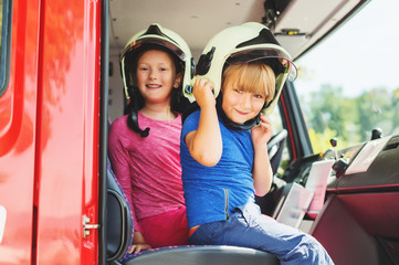 Two cute kids playing in fire truck, pretending to be firefighters, open doors day at fire station. Future profession for children. Educational program for schoolkids